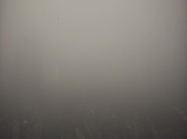 Vista da janela mostra densa neblina marrom impedindo a visualização dos prédios